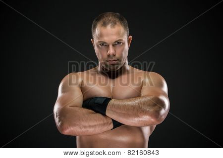 studio portrait of young caucasian boxer with folded hands posing ark background