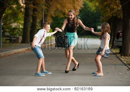 Mother With Naughi Son Adn Daughter On A Walk In Park