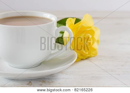 Cup of tea with a single yellow rose