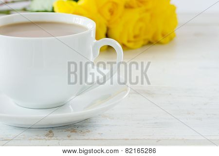 Cup of tea with a bouquet of yellow roses