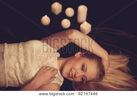 Young Blonde Woman On Black Sheets With Candels In Background