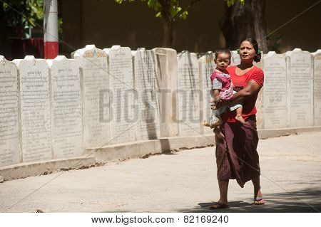 Burmese Mother And Son Through The Ranks Of The Stone Slabs Of The Buddhist Canon(Tripitaka Texts).