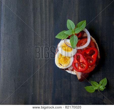 Sandwich with egg and pepper basil on a wooden surface