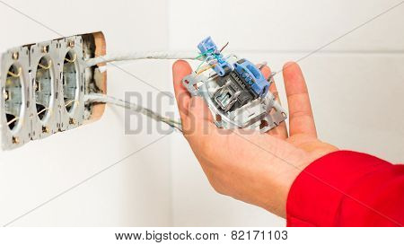 Electrician Mounting Electrical Wall Outlet