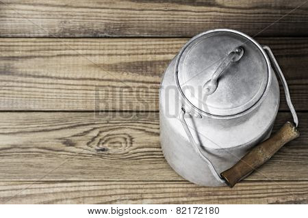 Aluminum old milk can on a wooden background in the horizontal format