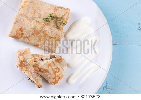 Stuffed crepes topped with sour cream.