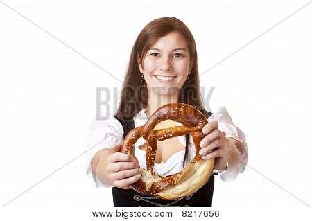 Young woman with Bavarian dirndl holding Oktoberfest pretzel.