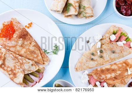 Thin pancakes, crepes with red caviar, salmon, pickled cucumbers and bacon