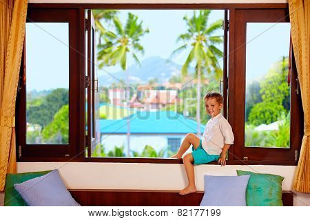 Cute Boy Sitting On Window Sill In Tropics