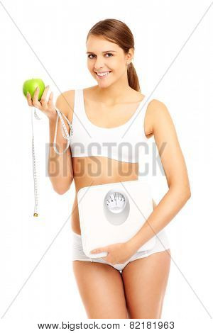 A picture of a fit woman with apple tape measure and bathroom scales