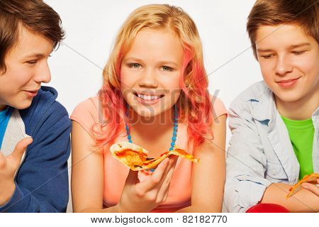 Happy smiling friends holding pizza pieces