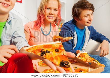 Smiling girl and boys holding pizza pieces at home