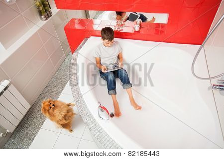 Boy hiding in the bathroom, playing in tablet. Computer Addiction, gambling, lie