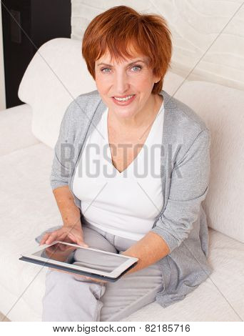 Mature woman with tablet pc. Female with computer at home