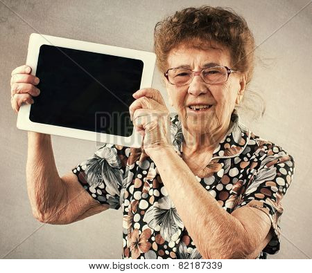 Old woman holding a tablet in the hands of. Seniors with tablet pc