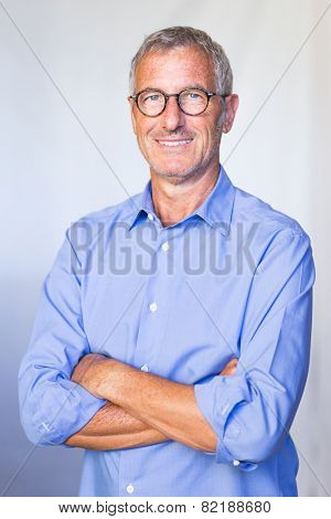 Portrait of a a successful mature handsome businessman smiling wearing a pair of glasses