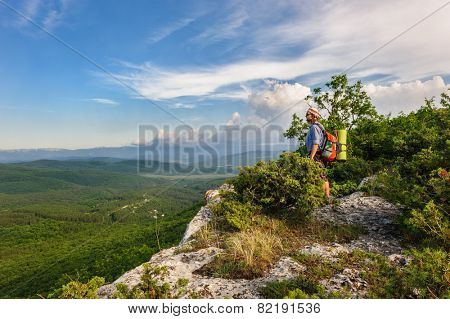 Hiking man in rays of sunset