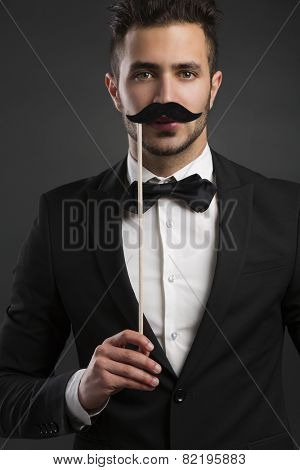 Handsome young man holding a fake mustache