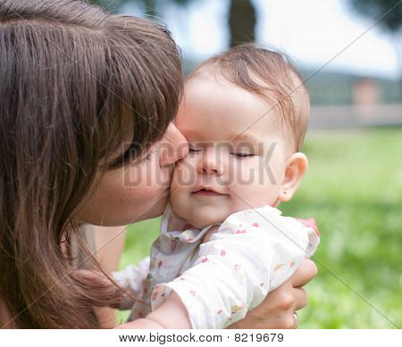 Mom Kisses Her Little Daughter, Played In The Park