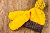 image of knitted cap  - yellow knitting cap and mittens on wooden background - JPG