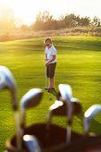 stock photo of golf bag  - Casual kid at a golf field holding golf club - JPG