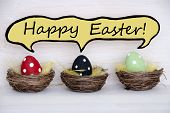 stock photo of easter basket eggs  - Three Colorful Red Black And Green Dotted Easter Eggs In Easter Baskets Or Nest On White Wooden Background With Comic Speech Balloon With English Text Happy Easter Used As Easter Decoration Or Easter Greetings - JPG
