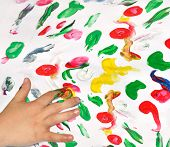 stock photo of finger-painting  - Painting with her fingers with different color paint - JPG