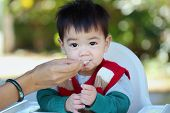 picture of child feeding  - mother feeding her baby and asian baby look at camera - JPG