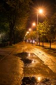stock photo of roof-light  - Paved Street with puddles in Old Riga Latvia at night - JPG