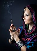 stock photo of namaste  - Woman wrapped in scarf holding incense stick in hands with Namaste gesture at dark background - JPG