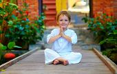 stock photo of cute  - cute boy trying to find inner balance in meditation - JPG