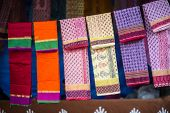 image of dupatta  - Various colorful fabrics and shawls at a market stall - JPG