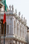 stock photo of vicenza  - One of the side of the Basilica palladiana in Vicenza with the town flag on the left - JPG