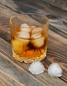 pic of scotch  - Glass with Scotch and ice on old wooden background - JPG