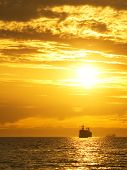 foto of sail ship  - Cargo ship sailing away against colorful sunset - JPG