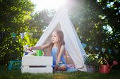 picture of teepee tent  - Adorable little girl having fun playing outdoors on summer day - JPG