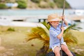 picture of tire swing  - Adorable little girl having fun on tire swing on summer day - JPG