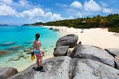 foto of virginity  - Young woman with snorkeling equipment enjoying view of a tropical beach standing on granite boulder at Virgin Gorda - JPG