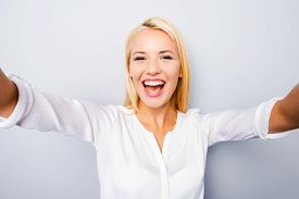 stock photo of adults only  - Cheerful young blond hair woman holding camera and making photo of herself while standing against grey background - JPG