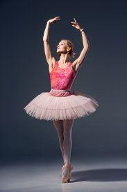 image of ballerina  - Portrait of the ballerina in ballet pose on a grey background - JPG