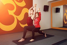 picture of sanskrit  - Mother and child yoga practice on the background of the Indian symbol of OM - JPG