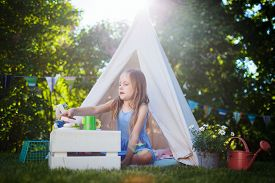 picture of tipi  - Adorable little girl having fun playing outdoors on summer day - JPG