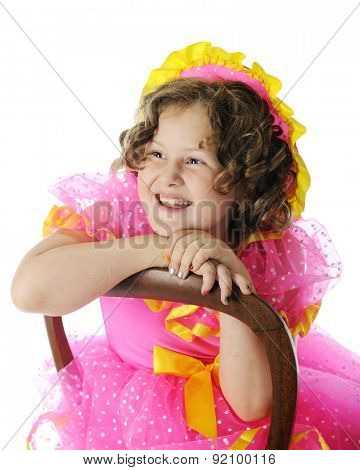 An elementary Shirely Temple impersonator laughing as she leans over the wooden back of a chair.  On a white background.