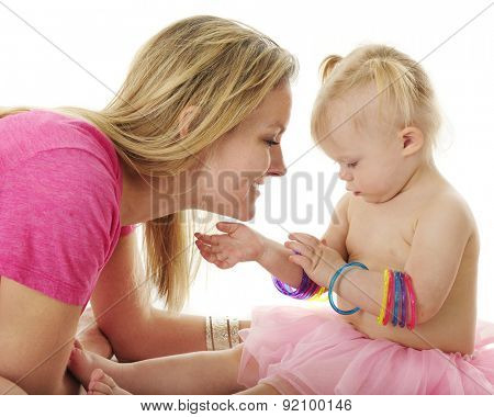 An admiring mother admiring the bangles that interest two year old daughter.  On a white background.l