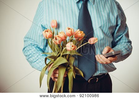 Businessman Dials Phone Number, Holding Tulips