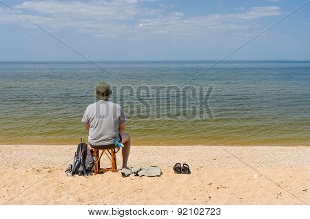 Lonely man sitting by the Dnepr river