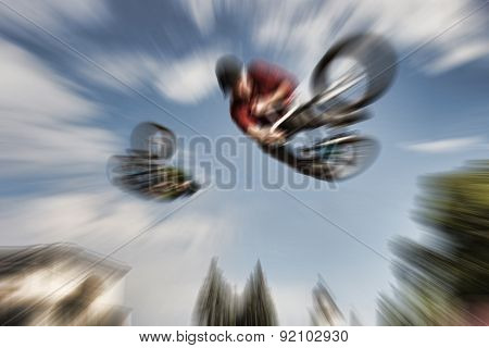 Abstract Background . Two Bmx Bikers High Up In The Air. Some Motion Blur On Both Bikers.