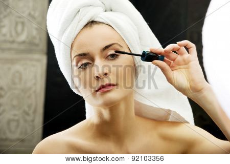 Woman using mascara in bathroom mirror.