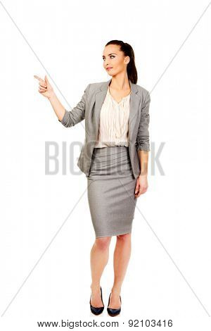 Beautiful confident businesswoman pointing up.