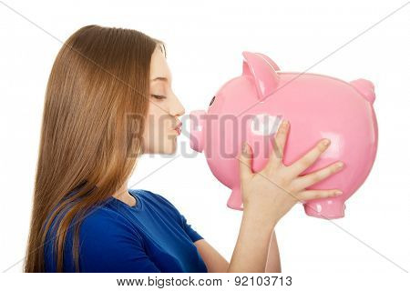 Happy teenage woman kissing piggybank.